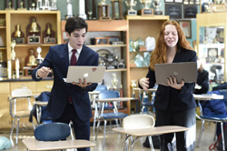 Two students standing and holding laptops give a spirited presentation